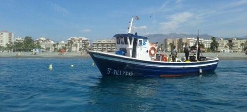Barco balizando una de las playas de la Costa Tropical