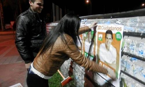 Una joven militante de Ciudadanos de Almuñécar colocando un cartel  para la campaña electoral al Parlamento de Andalucía