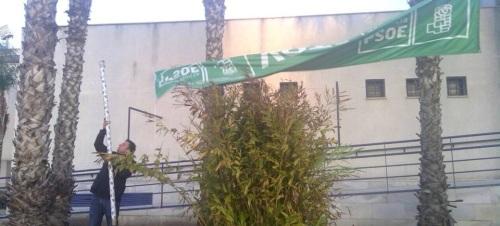 Un militante socialista retira una pancarta del PSOE tras las elecciones autonómicas