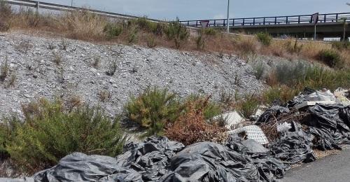 Depósito ilegal de plásticos agrícolas en la cuneta de un camino