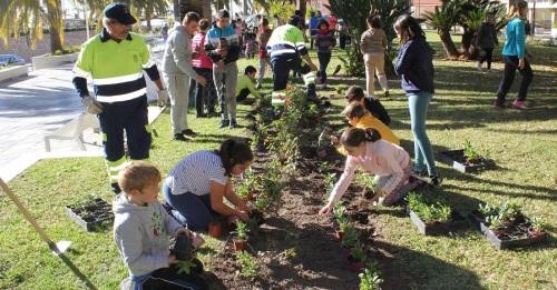 Alumnos de los colegios Reina Fabiola y Luis Pastor plantan flores en los jardines del paseo de las Explanadas