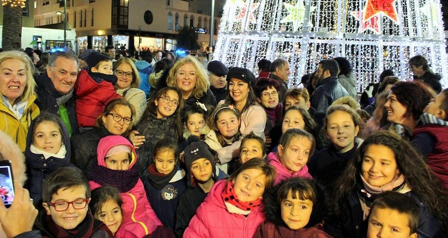 Flor Almón y miembros del equipo de Gobierno con los niños y niñas en el encendido del alumbrado de navidad