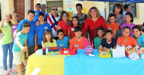 Foto archivo Flor Almón y Mercedes Sánchez junto a los niños y niñas del CEIP Arco Iris en la I Feria del Emprendimiento