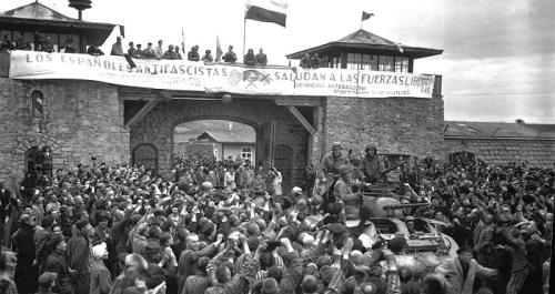 Prisioneros de Mauthausen saludan a la 11ª División Acorazada de los EE UU por su liberación bajo una pancarta escrita en español sobre sábanas castrenses